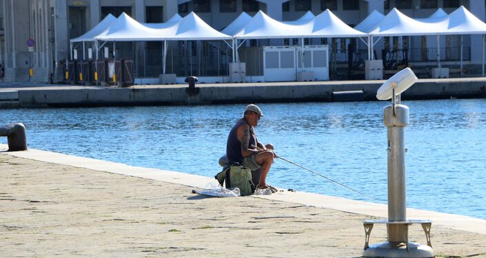 Un pescatore vicino alla Piazza Unità d'Italia