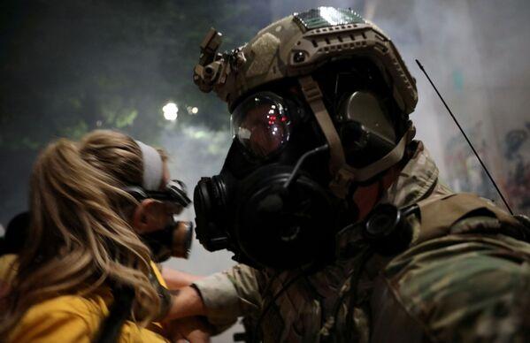 Un ufficiale federale delle forze dell'ordine respinge una donna durante una manifestazione contro  la disuguaglianza razziale a Portland, Oregon, USA, il 21 luglio 2020 - Sputnik Italia