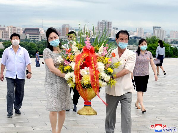 Nordcoreani portano fiori alle statue di Kim Il-sung e Kim Jong-il. - Sputnik Italia