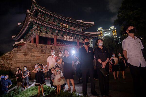 Persone con le mascherine si sono radunate alla Porta Taedong a Pyongyang per guardare i fuochi d'artificio. - Sputnik Italia