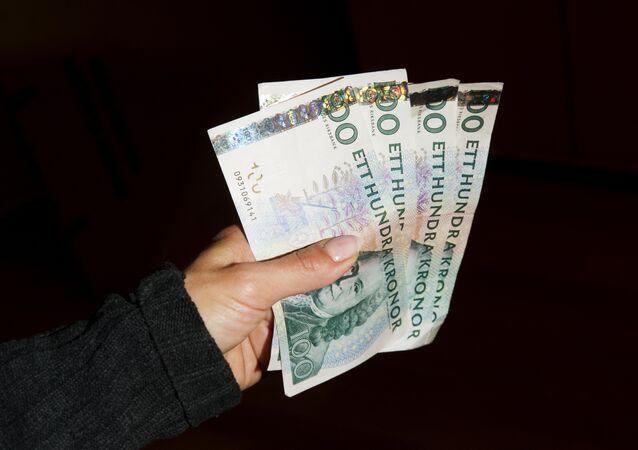 Una donna regge delle banconote di corone svedesi