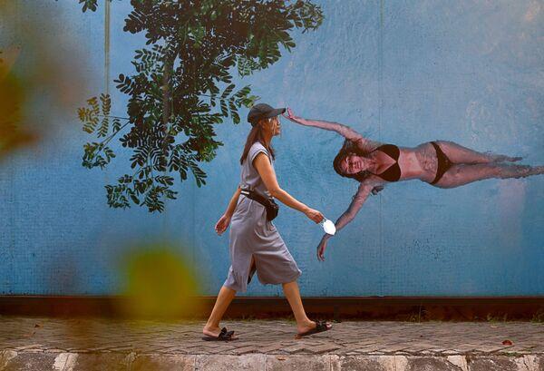 Una donna che indossa uno scudo facciale cammina lungo una strada a Jakarta, Indonesia, il 29 luglio 2020 - Sputnik Italia