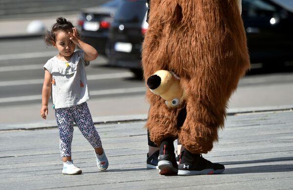 Una bambina guarda un artista di strada che indossa un costume da orso nel centro della capitale ucraina di Kiev durante una calda giornata estiva il 24 luglio 2020 - Sputnik Italia
