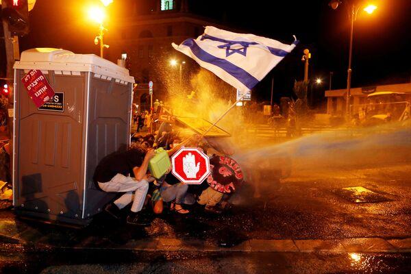 La polizia usa il cannone ad acqua durante una protesta contro la presunta corruzione del primo ministro israeliano Benjamin Netanyahu e la gestione da parte del suo governo della crisi del coronavirus, vicino alla sua residenza a Gerusalemme il 26 luglio 2020 - Sputnik Italia