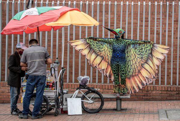 Una persona vestita da colibrì si esibisce durante la cosiddetta strategia Alas de distancia per promuovere pratiche di auto-cura, principalmente di distanza fisica, come misura preventiva contro la diffusione del coronavirus COVID-19, a Bogotà, il 24 luglio 2020 - Sputnik Italia