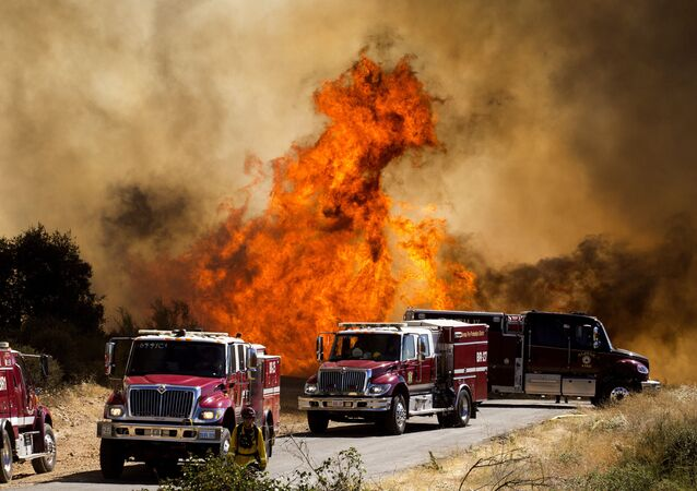 Fiamme dietro i camion dei pompieri all'Apple Fire di Cherry Valley, California, sabato 1 agosto 2020. Un incendio a nord-ovest di Palm Springs è divampato sabato pomeriggio, spingendo le autorità a emettere nuovi ordini di evacuazione mentre i vigili del fuoco hanno combattuto l'incendio di triplo- grado di calore