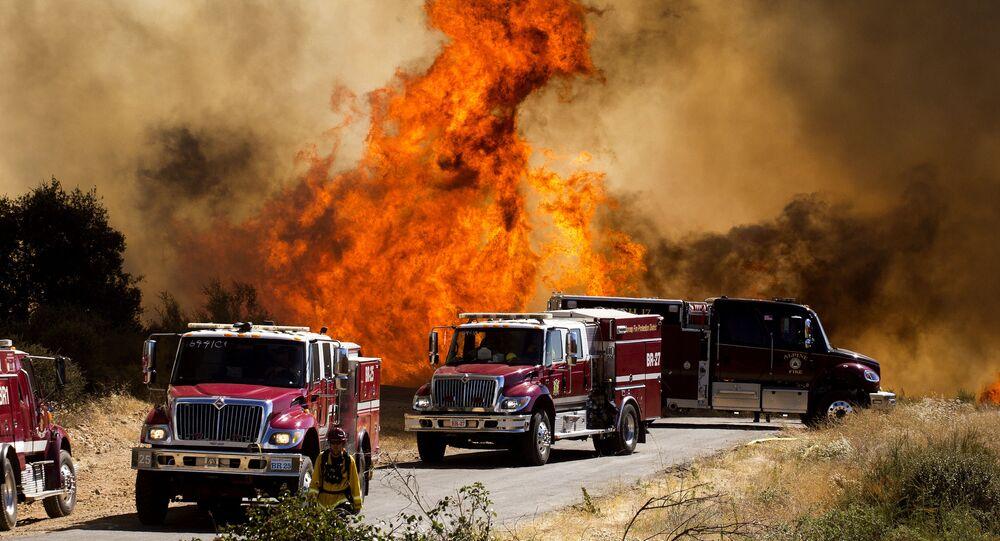 Fiamme dietro i camion dei pompieri all'Apple Fire di Cherry Valley, California, sabato 1 agosto 2020. Un incendio a nord-ovest di Palm Springs è divampato sabato pomeriggio, spingendo le autorità a emettere nuovi ordini di evacuazione mentre i vigili del fuoco hanno combattuto l'incendio di triplo- grado di calore