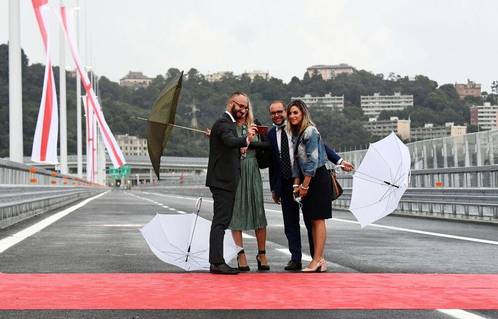 La gente si fa selfie sullo sfondo del nuovo ponte di Genova San Giorgio.