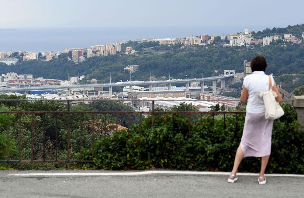 Una donna guarda il nuovo ponte di Genova.
