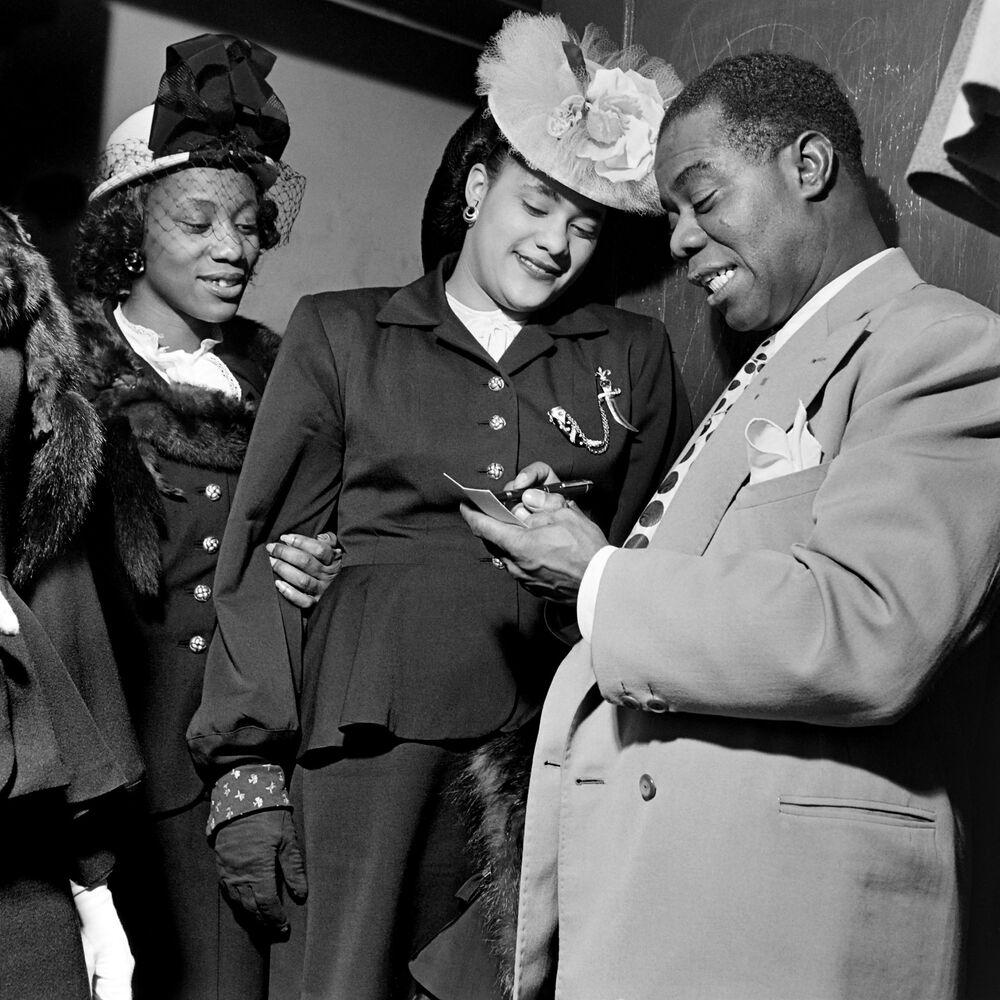 Il musicista americano Louis Armstrong con le fan a New York, 1950.