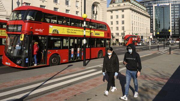 Persone con mascherine a Londra - Sputnik Italia