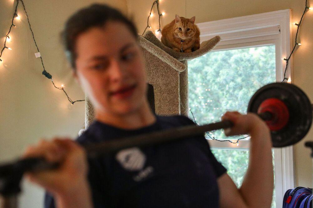 Un gatto tigrato guarda la sua padrona mentre si allena, la schermitrice americana Katherine Holmes a Princeton, nel New Jersey