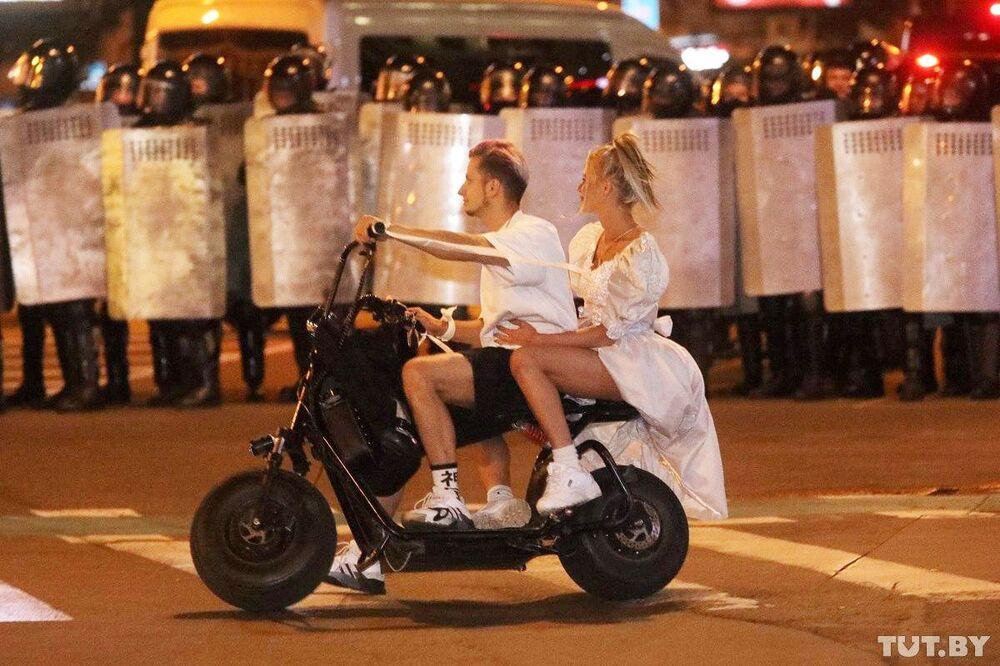 Una coppia va sullo scooter davanti ai poliziotti durante le proteste a Minsk.