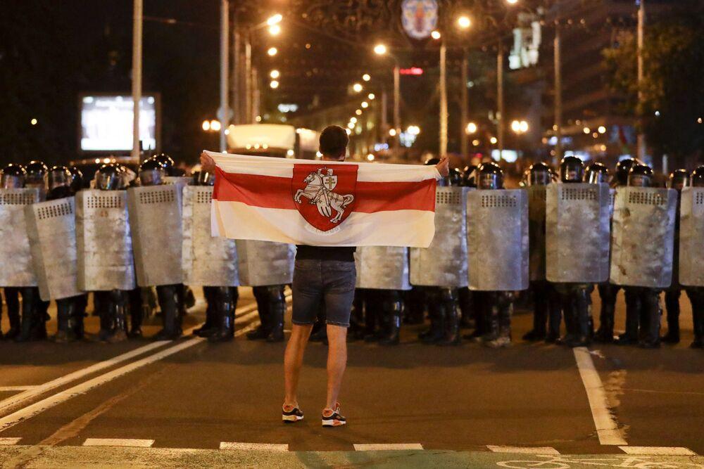 Un manifestante tiene una vecchia bandiera nazionale bielorussa stando davanti alla polizia durante le proteste dopo le elezioni presidenziali a Minsk.