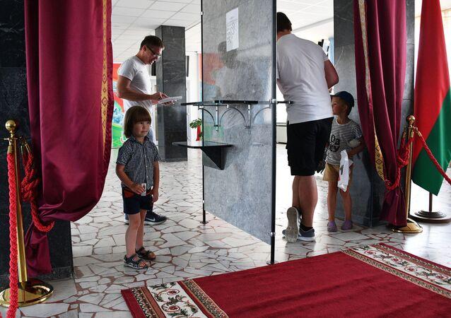 Degli uomini votano alle elezioni presidenziali di Bielorussia a Minsk