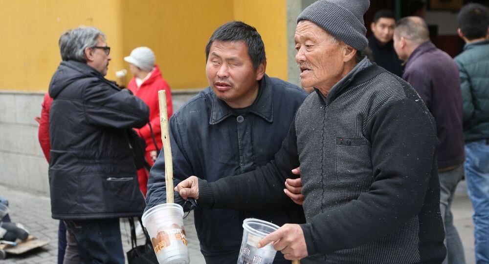 Mendicanti al Tempio del Buddha di Giada Yufosa a Shanghai.