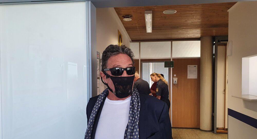 John McAfee all'aeroporto in Norvegia mentre indossa un tanga come mascherina