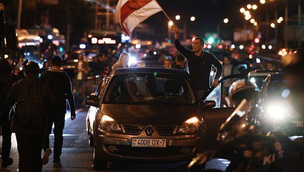Un'auto con la bandiera della Repubblica di Bielorussia (dei 1991-1995) va per le strade a Minsk durante una protesta dopo le elezioni presidenziali. - Sputnik Italia