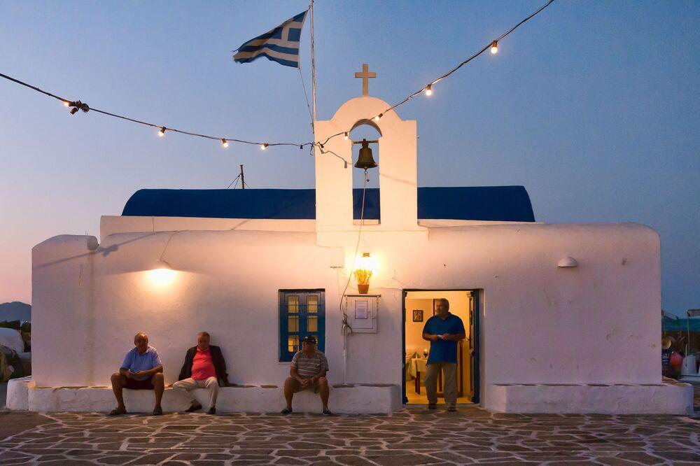 Dei pescatori davanti a una chiesa nel porto di Naoussa, Grecia.