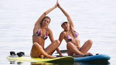 L'atleta russa Yuliya Boyarintseva tiene una sessione di yoga sulle paddle board con una sua studentessa sul fiume Enisej.