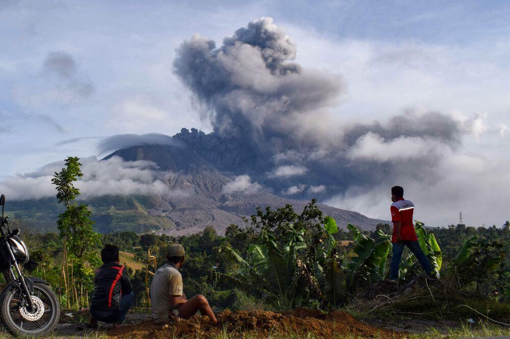 Gli abitanti di un villaggio osservano l'eruzione del vulcano Sinabung in Sumatra.