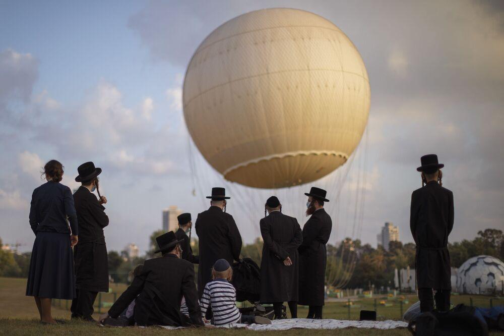 Degli ebrei ultra ortodossi in mascherine protettive nel parco di Tel Aviv, Israele.