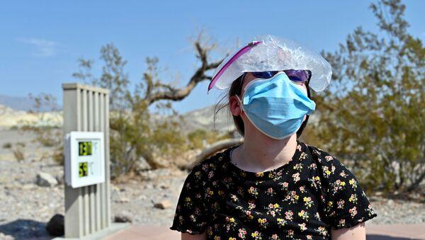 Una ragazza con un sacco di ghiaccio sulla testa in visita al parco nazionale La Valle della Morte, California, USA. - Sputnik Italia