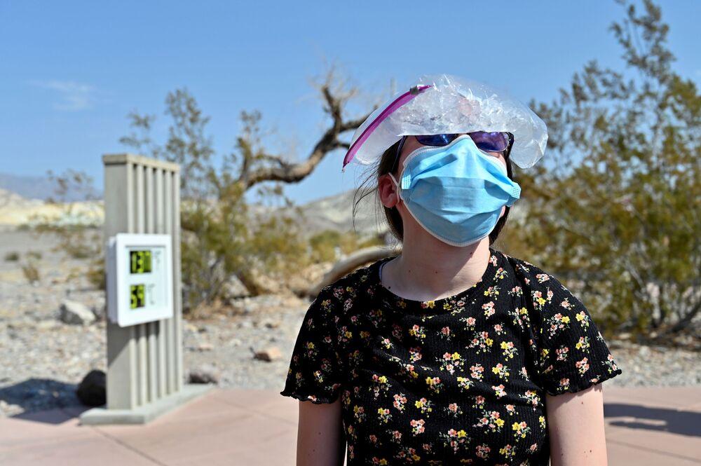 Una ragazza con un sacco di ghiaccio sulla testa in visita al parco nazionale La Valle della Morte, California, USA.