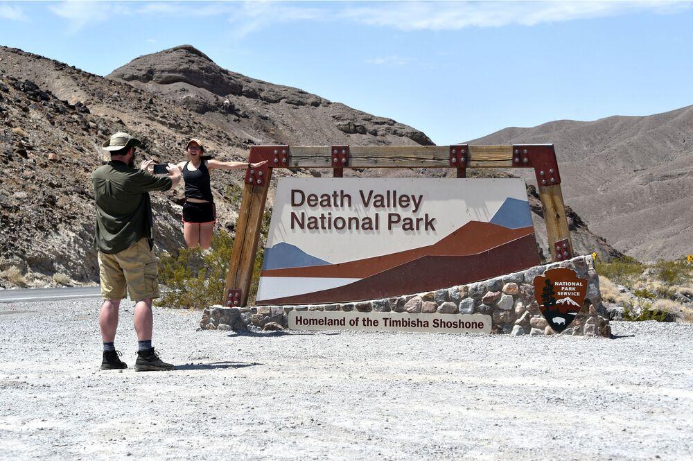 Dei turisti si fanno fotografare all'ingresso del parco della Valle della Morte.