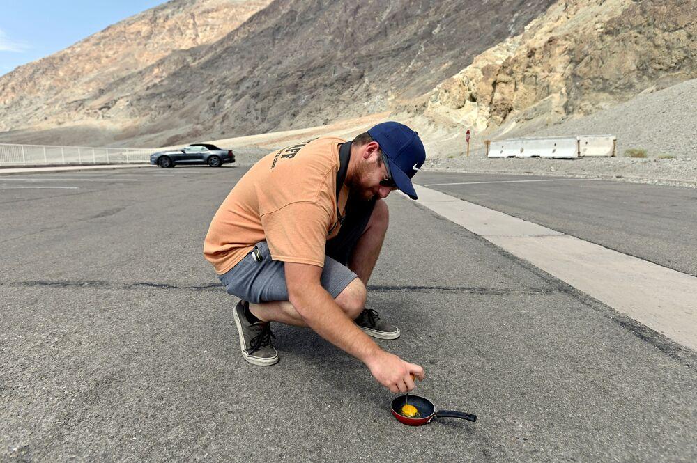 Un uomo fa un frittata sulla strada nel parco della Valle della Morte.