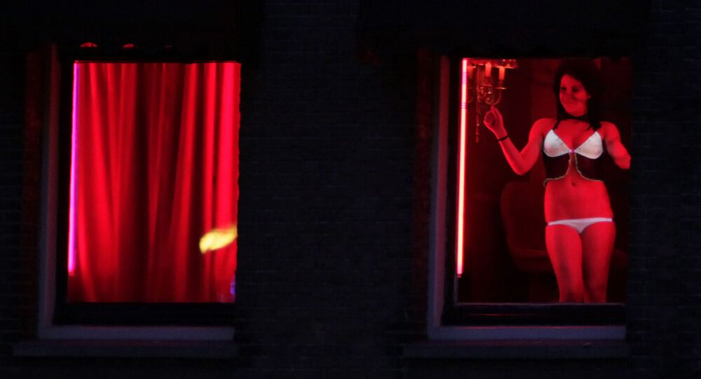 In this photo taken Monday Jan. 10, 2011 a prostitute advertises her wares behind red-lit windows in Amsterdam, Netherlands