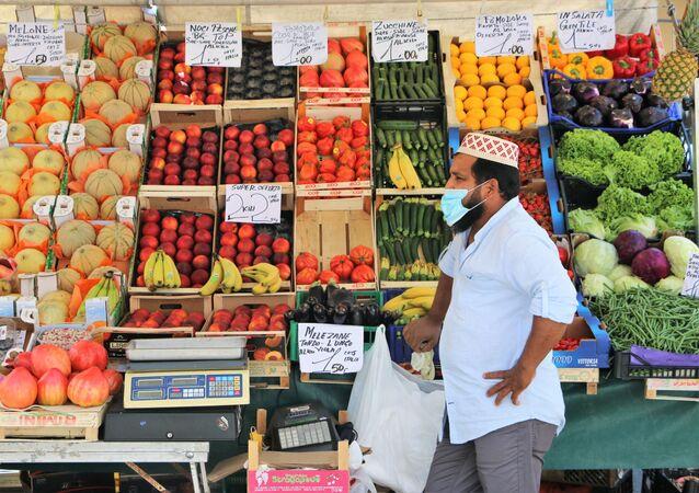 Un venditore straniero al mercato ortofrutticolo