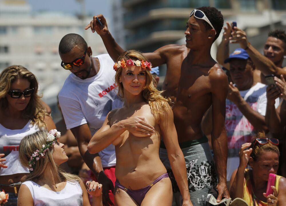 Ballerina in topless posa in una spiaggia a Rio de Janeiro.