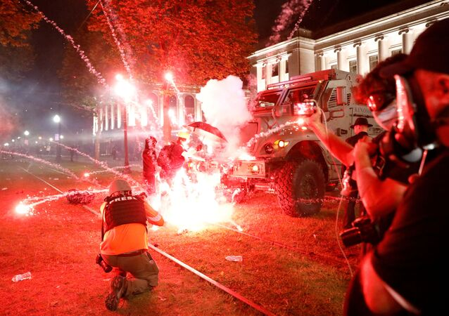 Flares go off in front of a Kenosha Country Sheriff Vehicle as demonstrators take part in a protest following the police shooting of Jacob Blake, a Black man, in Kenosha, Wisconsin, U.S. August 25, 2020.