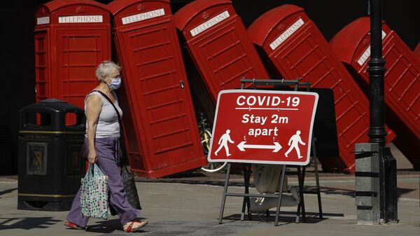 Женщина в медицинской маске и плакат с призывом соблюдать социальную дистанцию на фоне скульптуры британского скульптора Дэвида Маха Out of Order в Лондоне, Великобритания  - Sputnik Italia
