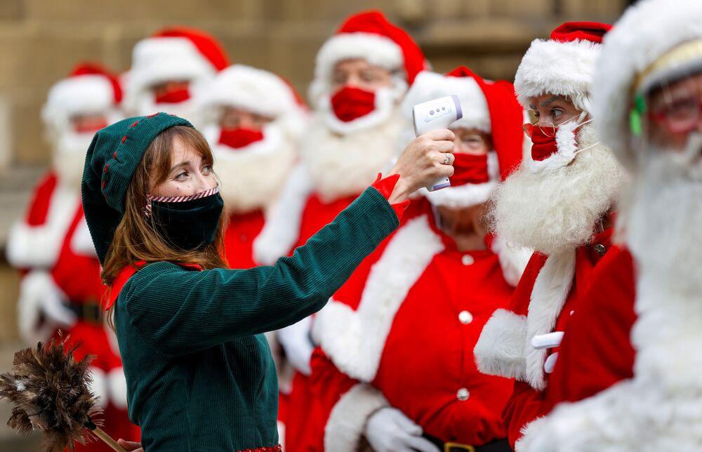 Una ragazza vestita da elfo posa per una foto con i laureati della Scuola di Santa Clause del Ministry of Fun a Londra.