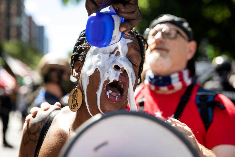 Una ragazza si lava gli occhi con del latte durante le proteste a Portland.