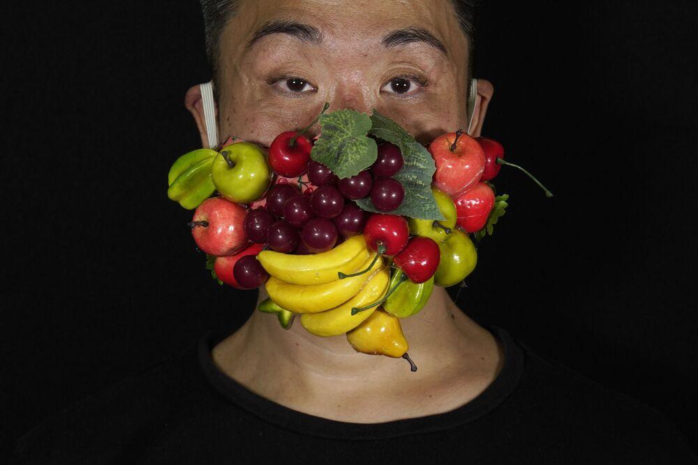 Edmond Kok, costumista e attore teatrale di Hong Kong, che indossa una maschera per il viso decorata con molti frutti diversi a Hong Kong giovedì 6 agosto 2020