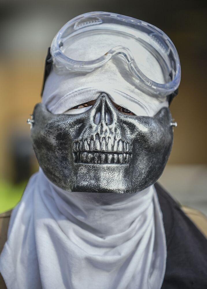 Un dimostrante che indossa una mascherina protettiva creativa durante una protesta a Bogotà, in Colombia