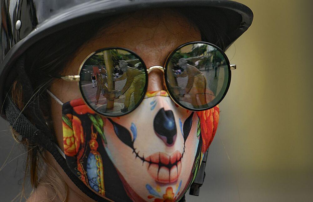 Una ragazza con occhiali da sole e una mascherina protettiva creativa contro il coronavirus a Caracas, in Venezuela