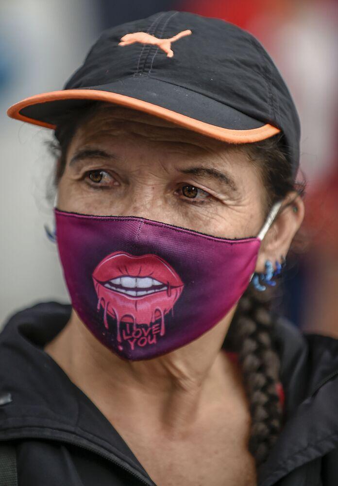 Una donna indossa una maschera per il viso come misura preventiva contro la diffusione del nuovo coronavirus COVID-19, durante una protesta contro il presidente colombiano Ivan Duque e il presunto stupro di ragazze indigene da parte di membri dell'esercito colombiano, a Bogotà il 10 luglio 2020
