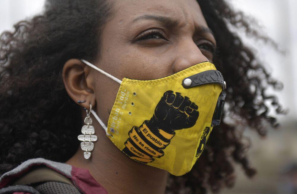Una donna che indossa una mascherina sul viso con la scritta Mannaggia, la gente non si arrende! prende parte a una protesta contro i recenti massacri a Bogotà il 28 agosto 2020
