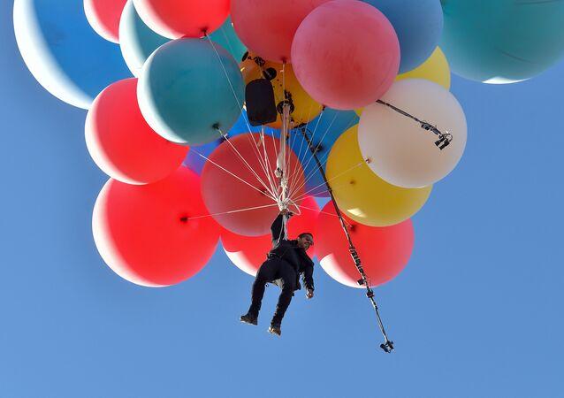 Incredibile impresa, quella dell'llusionista David Blaine che, aggrappato a 52 palloni pieni di elio, ha sorvolato raggiungendo circa i 7mila metri di altitudine, il deserto dell'Arizona, il 2 settembre 2020