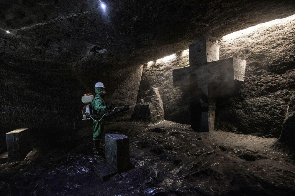 Un operaio disinfetta la Cattedrale di sale di Zipaquira, una chiesa sotterranea costruita in una miniera di sale, a Zipaquira, 45 km a nord di Bogotà, il 30 agosto 2020, durante la pandemia di coronavirus COVID-19