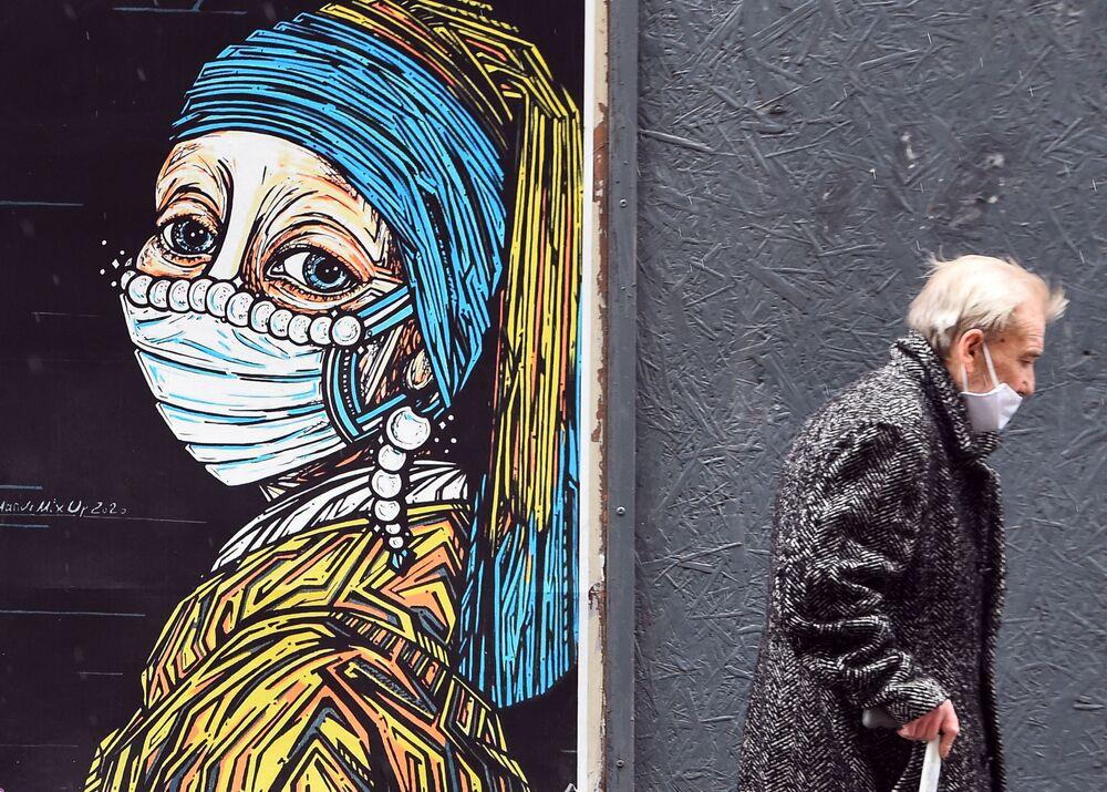 Graffiti con il dipinto di Jan Vermeer La ragazza con l'orecchino di perla in una mascherina protettiva