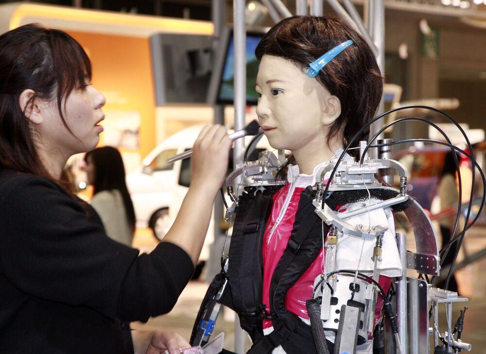 Una truccatrice applica il trucco a un robot umanoide di nome Pikarin alla mostra sull'assistenza domiciliare e la riabilitazione a Tokyo, il 3 ottobre 2007