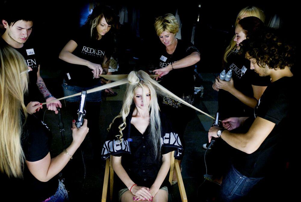 I parrucchieri fanno i capelli a una modella prima di una sfilata di moda a Copenaghen