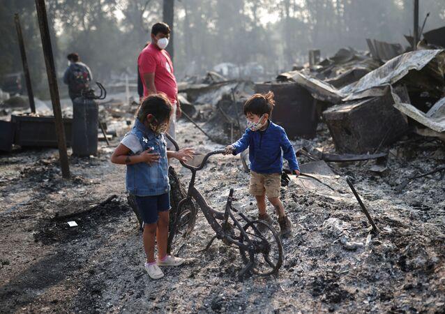 Ashley, 3 anni, ed Ethan, 2 anni, guardano una bicicletta bruciata dopo che gli incendi hanno distrutto un quartiere a Bear Creek, Phoenix, Oregon, Stati Uniti, 10 settembre 2020.