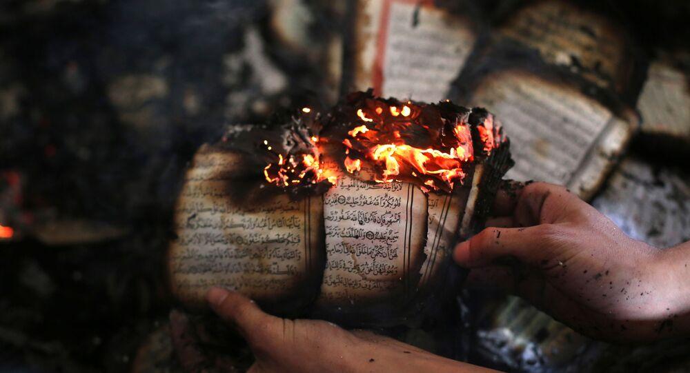 Un uomo palestinese mostra una copia del libro sacro dell'Islam, il Corano, ancora in fiamme all'interno di una moschea che è stata incendiata dai coloni israeliani ad al-Mughayir, nella Cisgiordania occupata vicino all'insediamento ebraico di Shilo, il 12 novembre 2014.