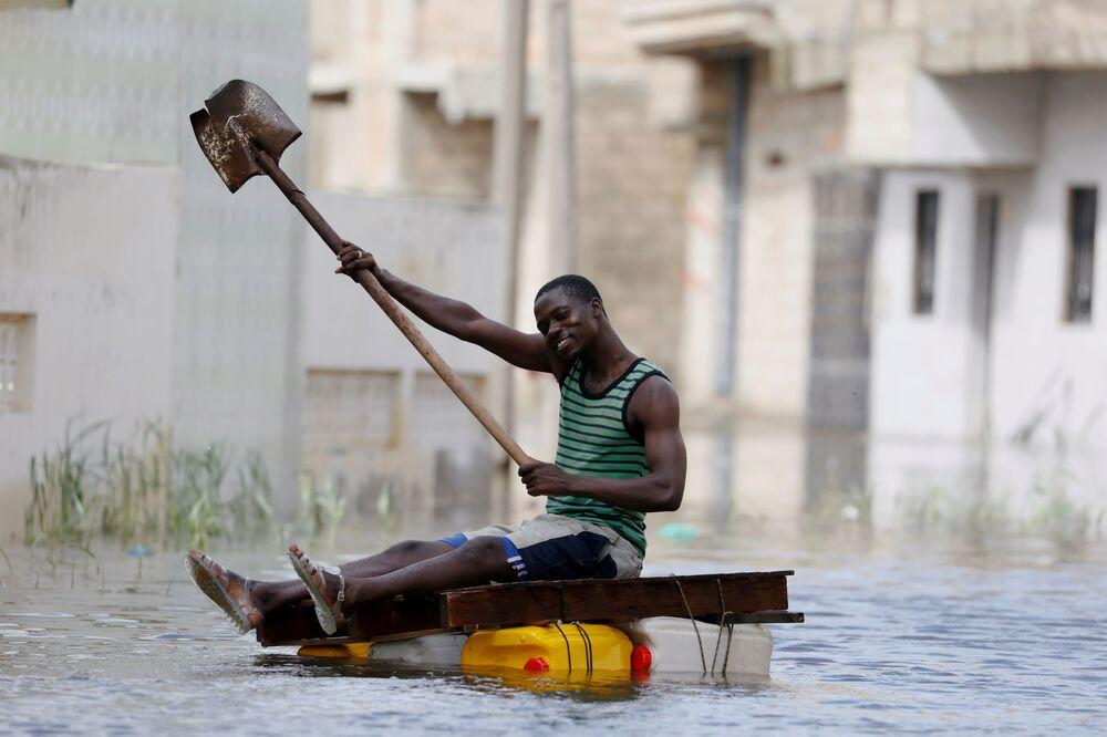 Uomo su un travamento improvvisato naviga sulle strade inondate dopo le piogge in Senigallia.